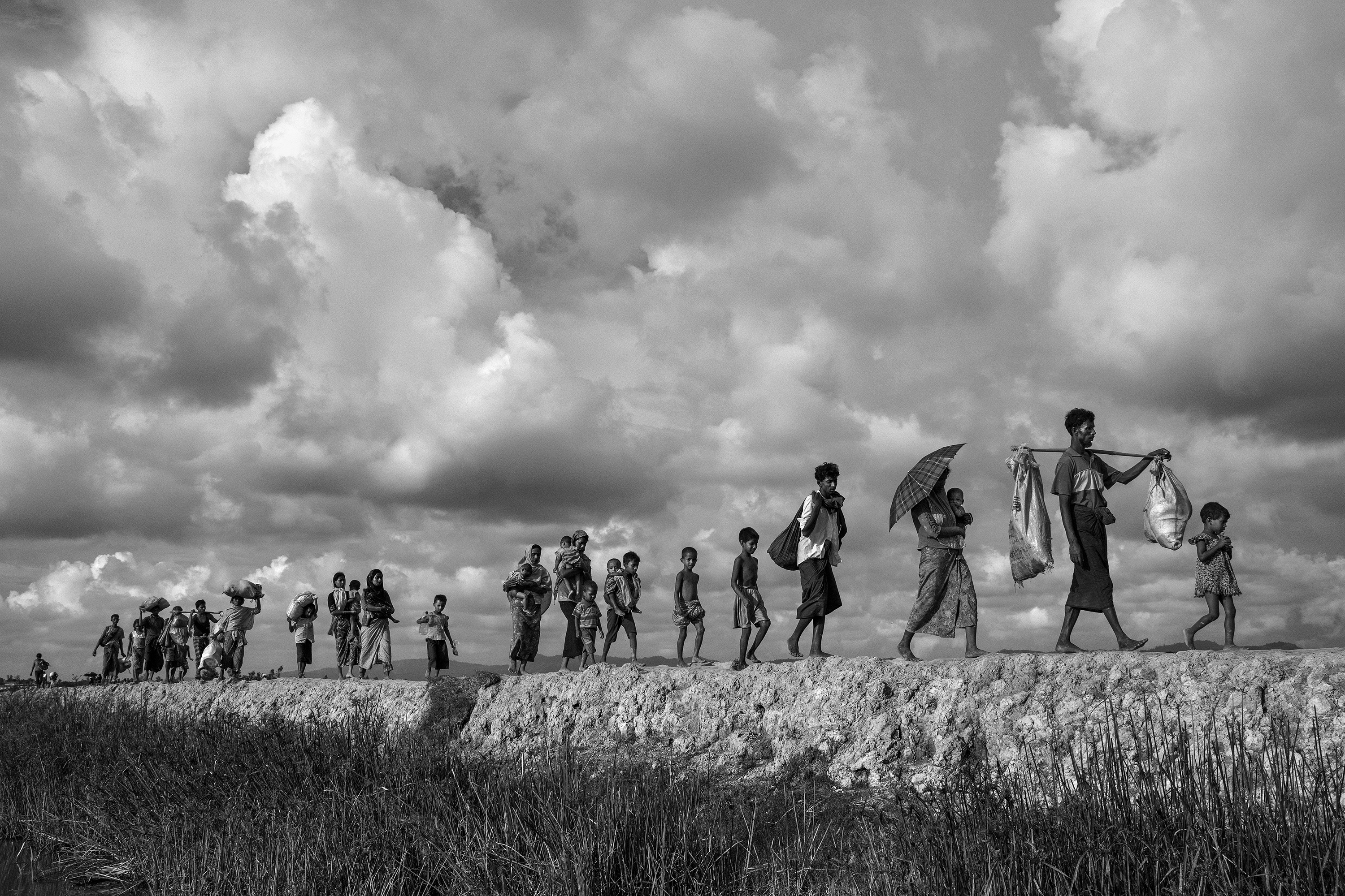 Rohingya refugees carry their belongings as they walk on the Bangladesh side of the Naf River after fleeing Myanmar.