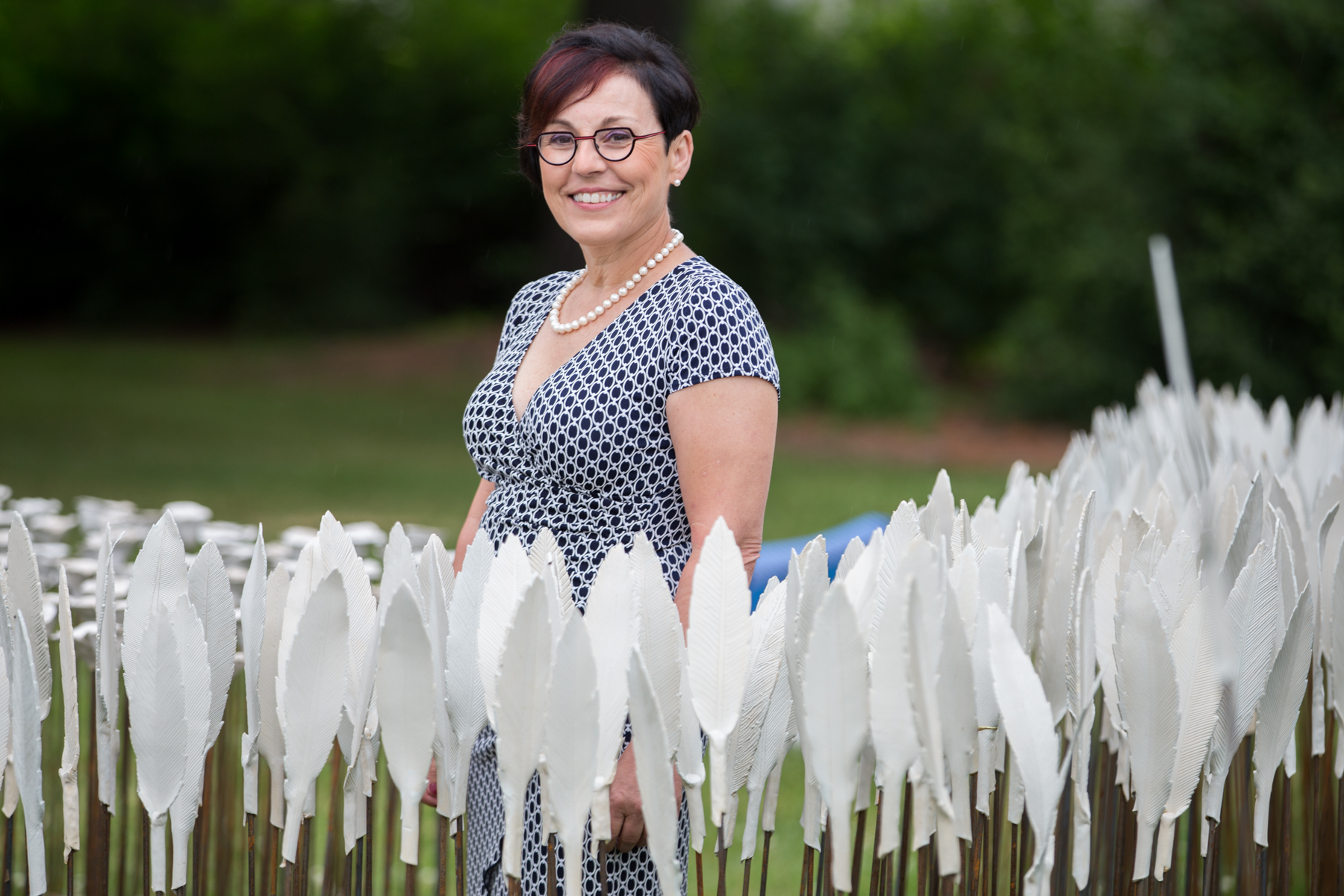 Artist Hilde Lambrechts stands among the ceramic feathers of her art installation Compass: Peace in All Directions on the front lawn of Canada's Centre for Geography and Exploration, during the exhibit's launch on Wednesday, June 27. (Photo: Ben Powless/Canadian Geographic)