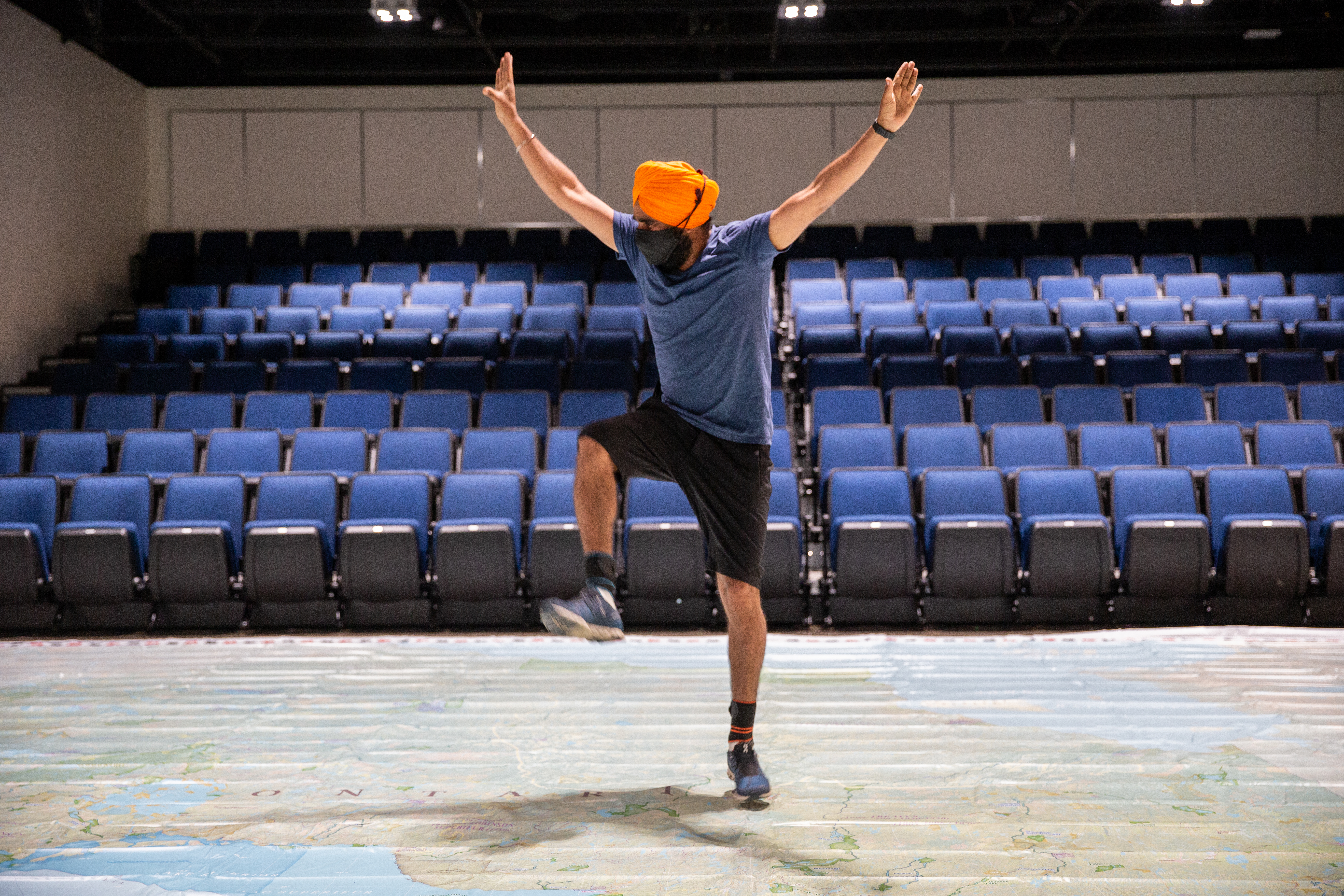 Gurdeep Pandher, who wears an orange turban, blue shirt and shorts, dances on a Giant Floor Map of Ontario in the Society's auditorium