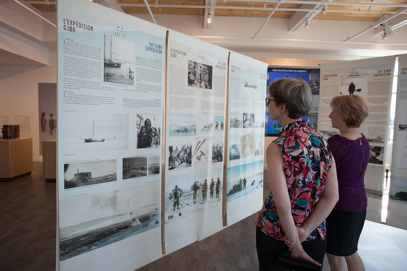 Two women read exhibit displays about polar explorer Roald Amundsen at 50 Sussex drive