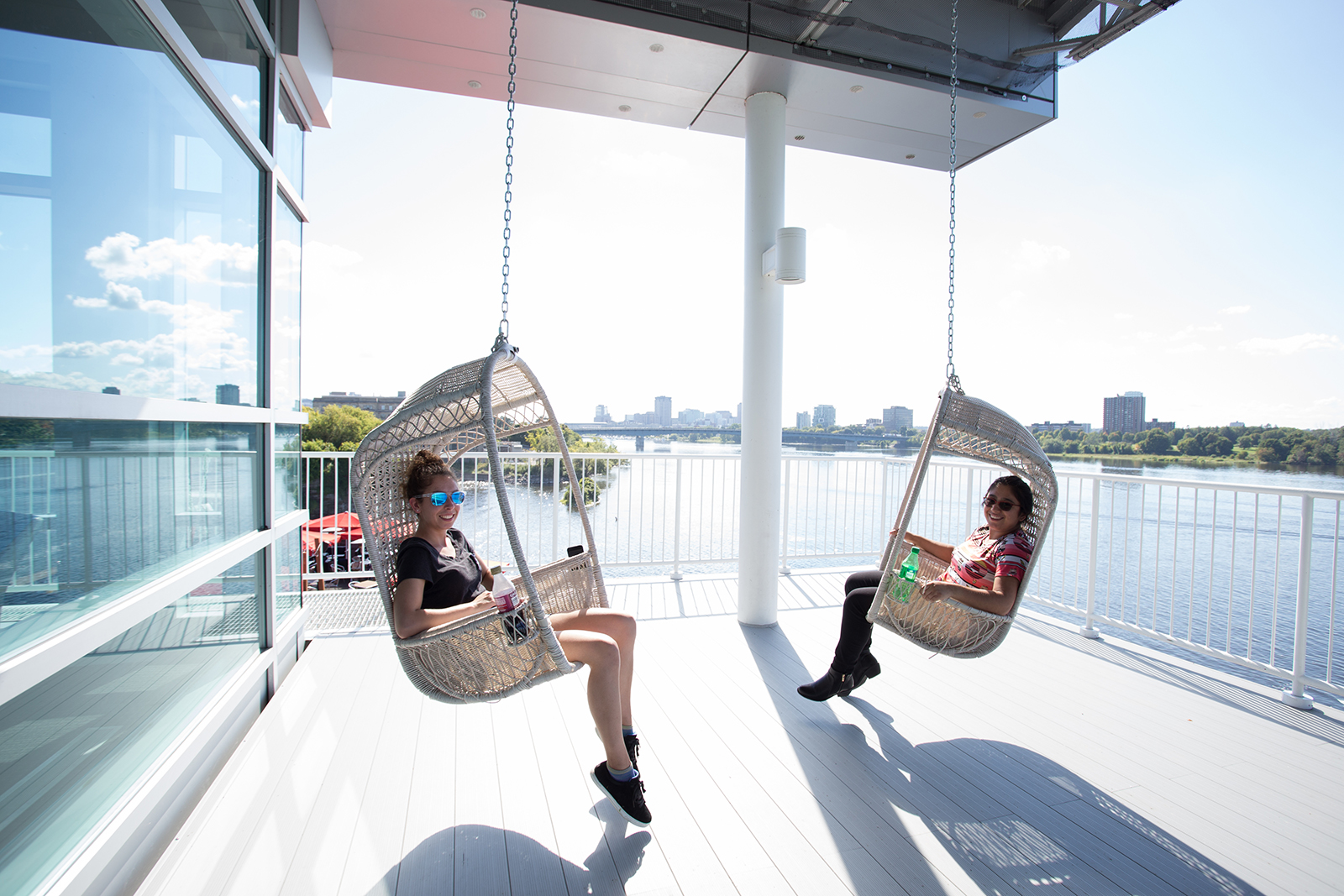 Teenage girls sit in two wicker swing chairs suspended from the roof of a balcony overlooking a river
