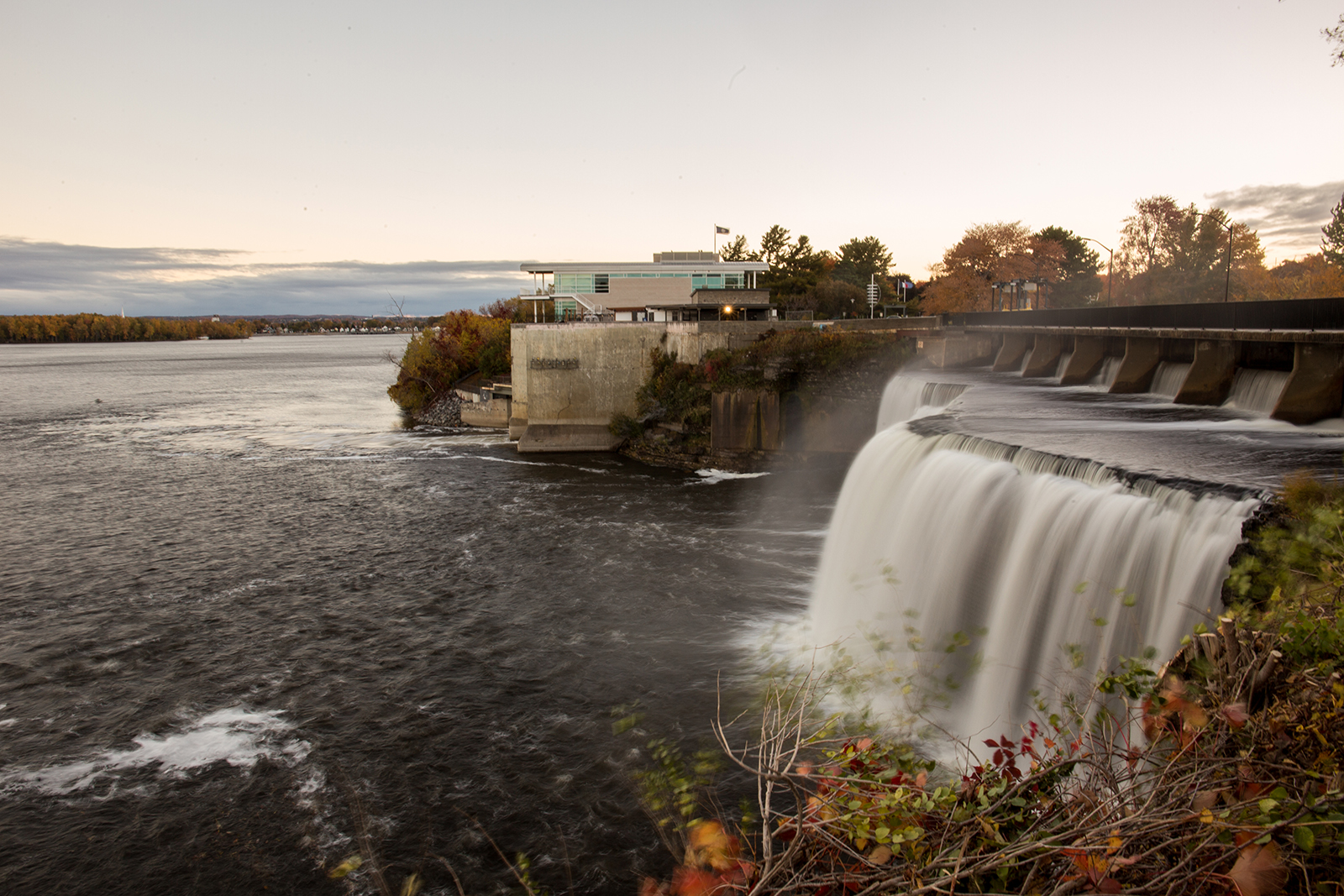 A landscape photo showing a glass building, 50 Sussex, behind a fast-flowing waterfall, the Rideau Falls