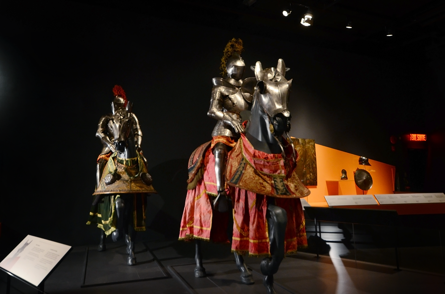 Museum display featuring two life-size knights in full body armour on horseback