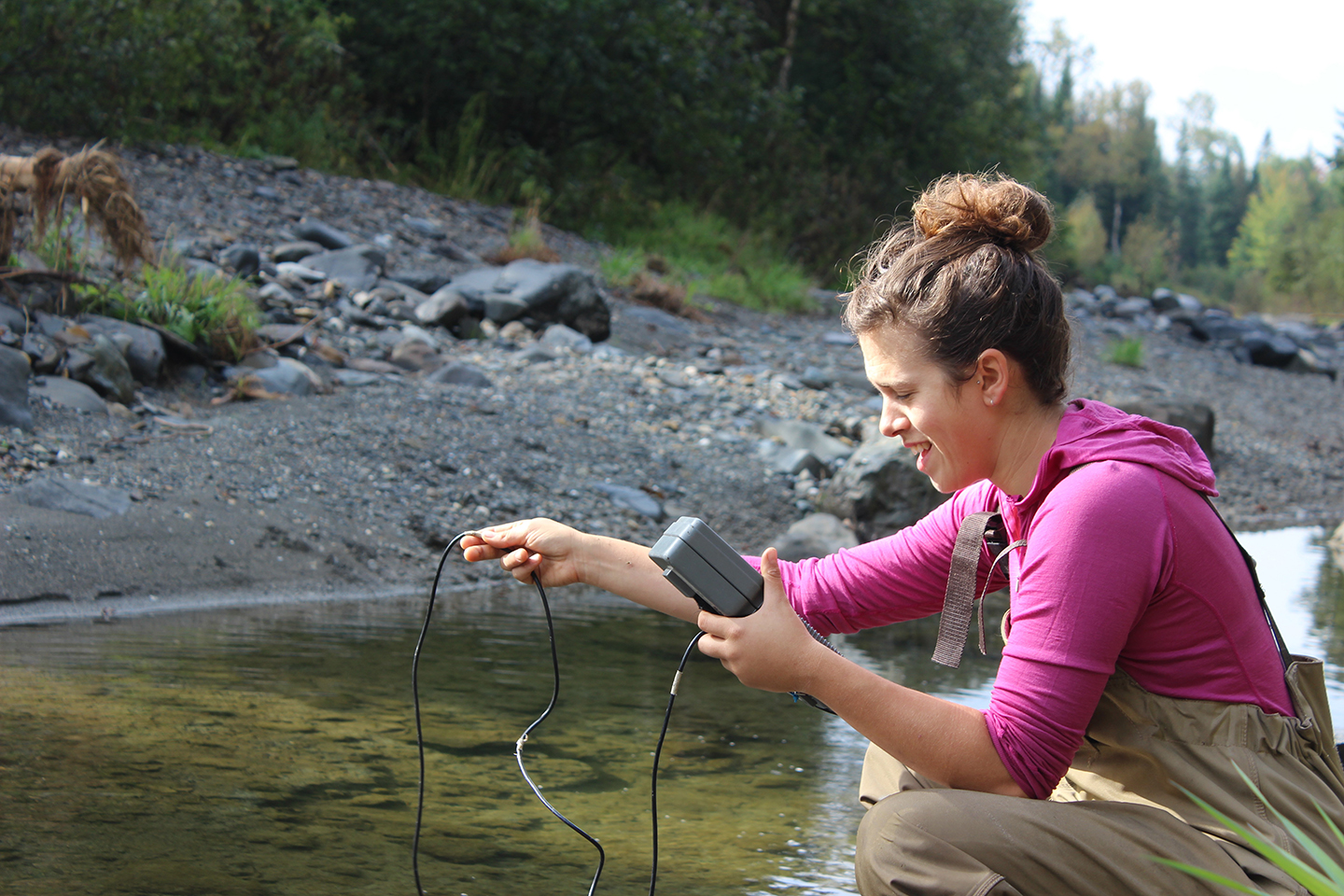 PhD candidate Dalal Hanna measuring water chemistry in a stream surrounded by a mix of agriculture and forests