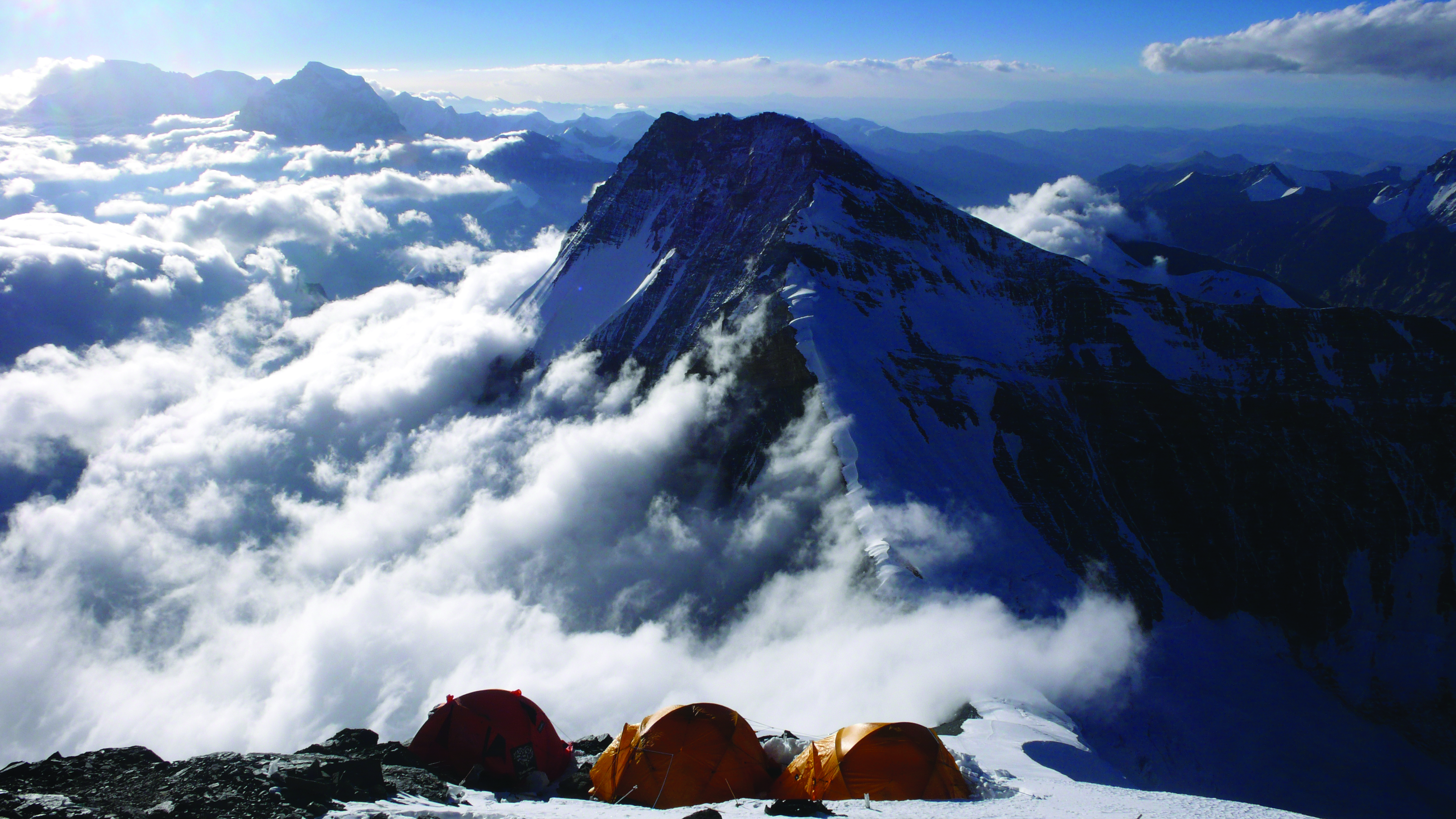 Tents pitched on mountain ridge descending into clouds