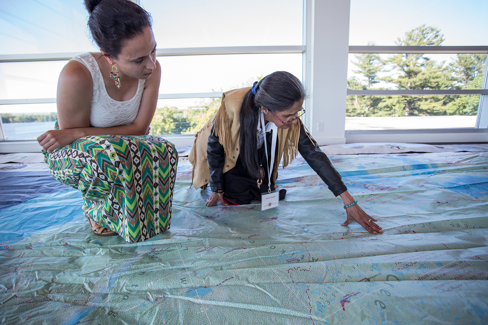 Two women explore a giant floor map