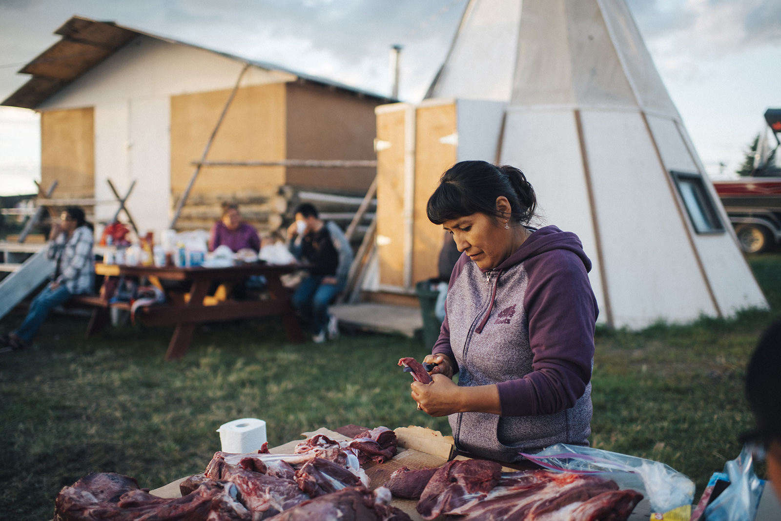 Diane Andre prepping caribou meat for her uncle's funeral.