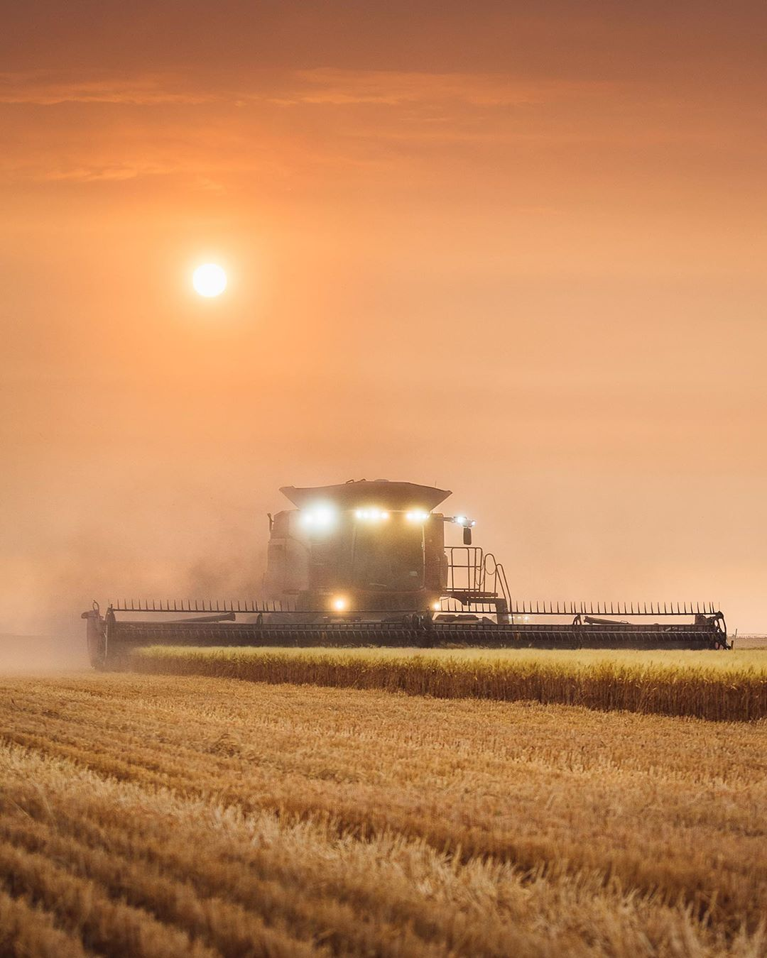 A farm machine plows the fields against an orange sky