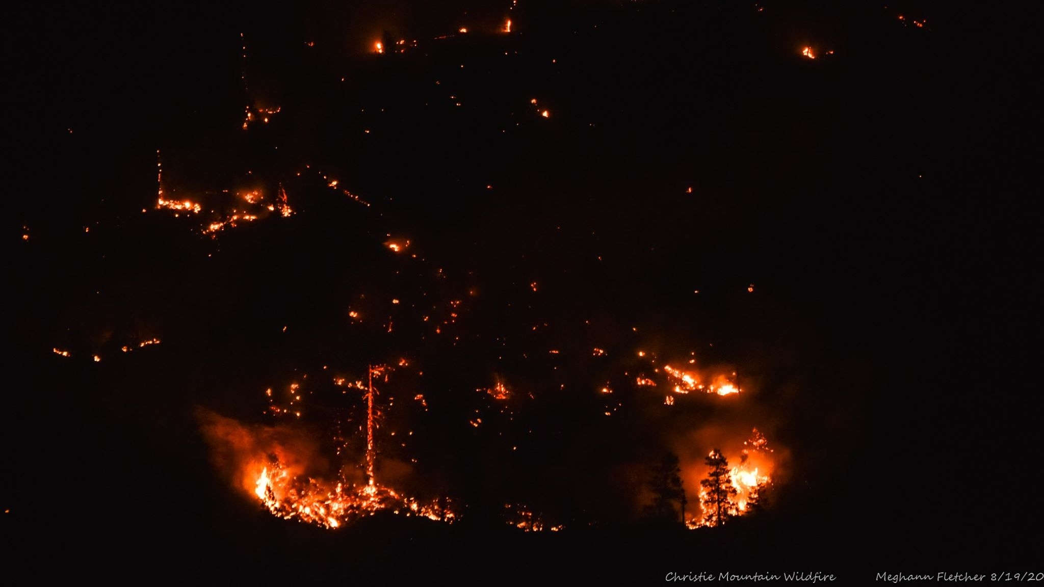 A wildfire burns after dark