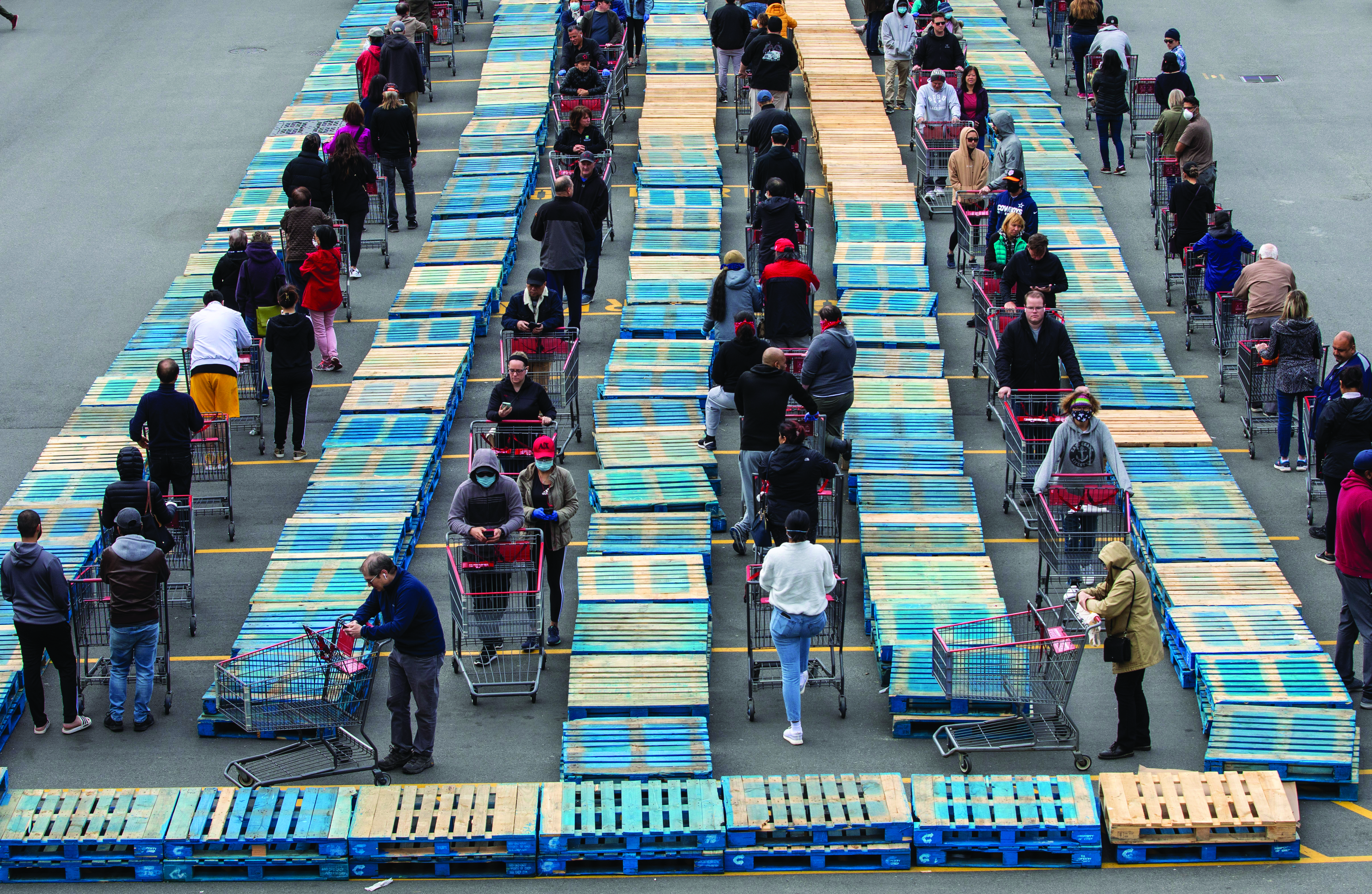 People with shopping carts wait in lines separated by pallets