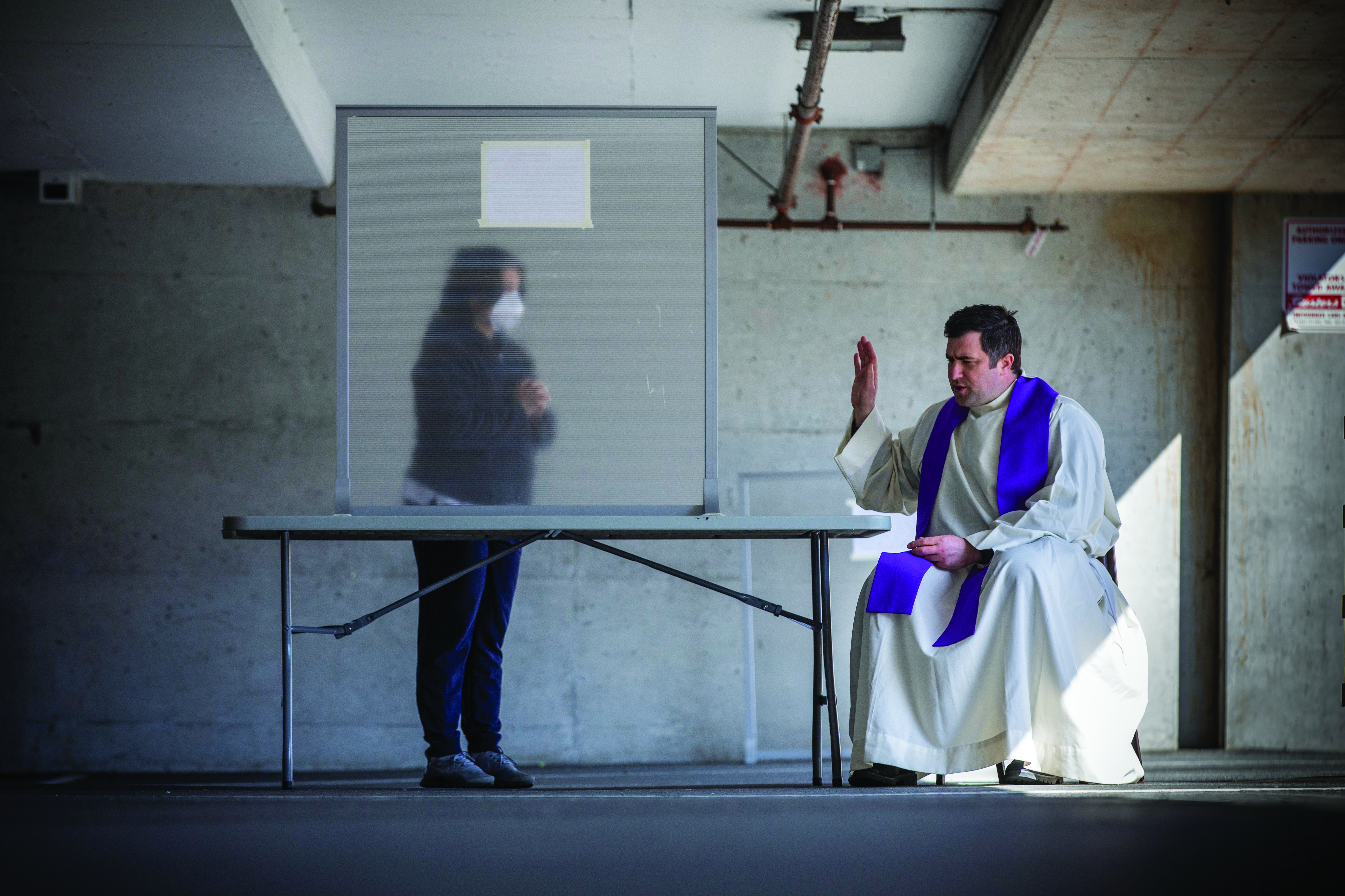 A woman in a mask stands behind a screen while a priest sits in front