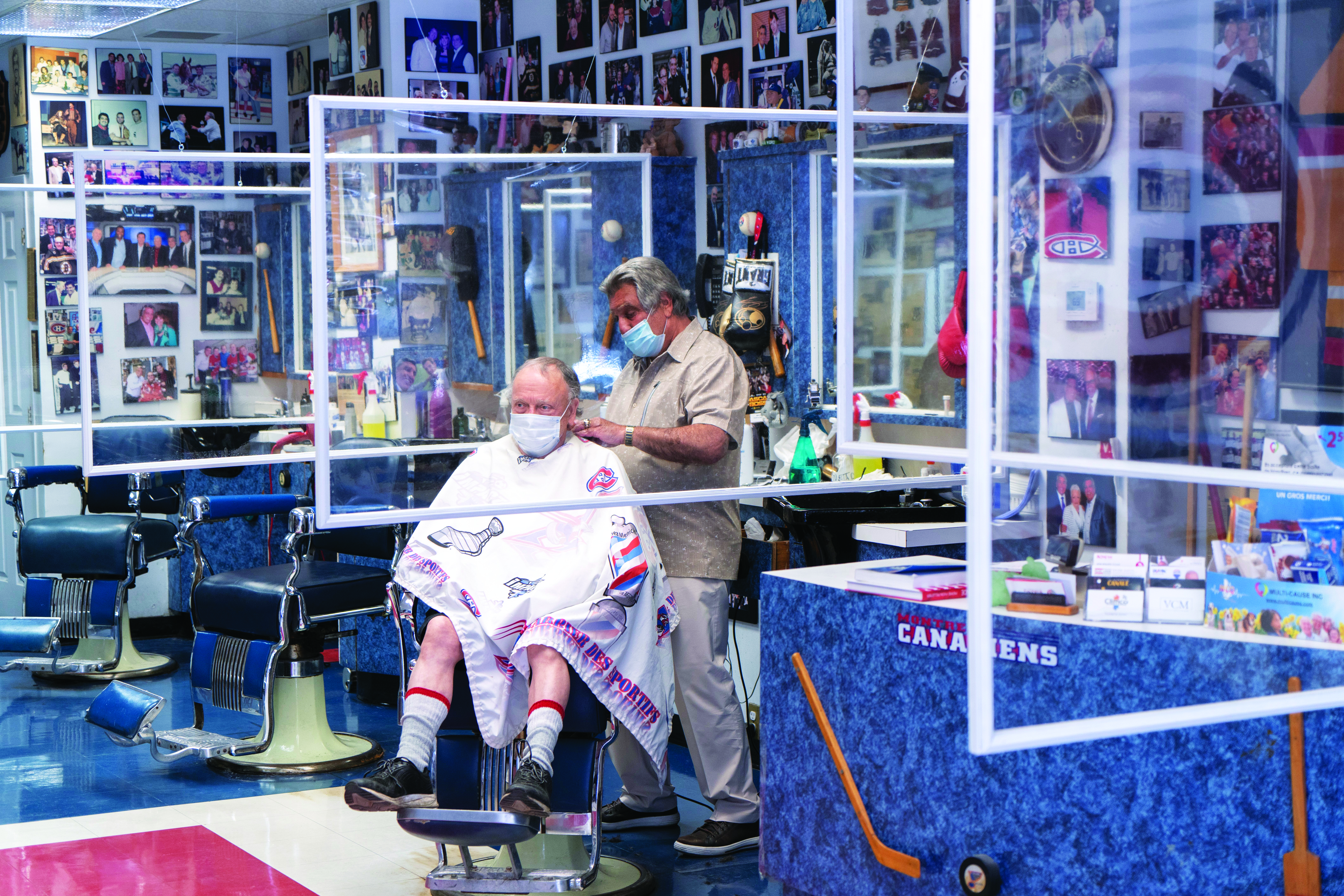 A man gets a haircut in a barber shop where people wear masks and plexiglass dividers separate clients