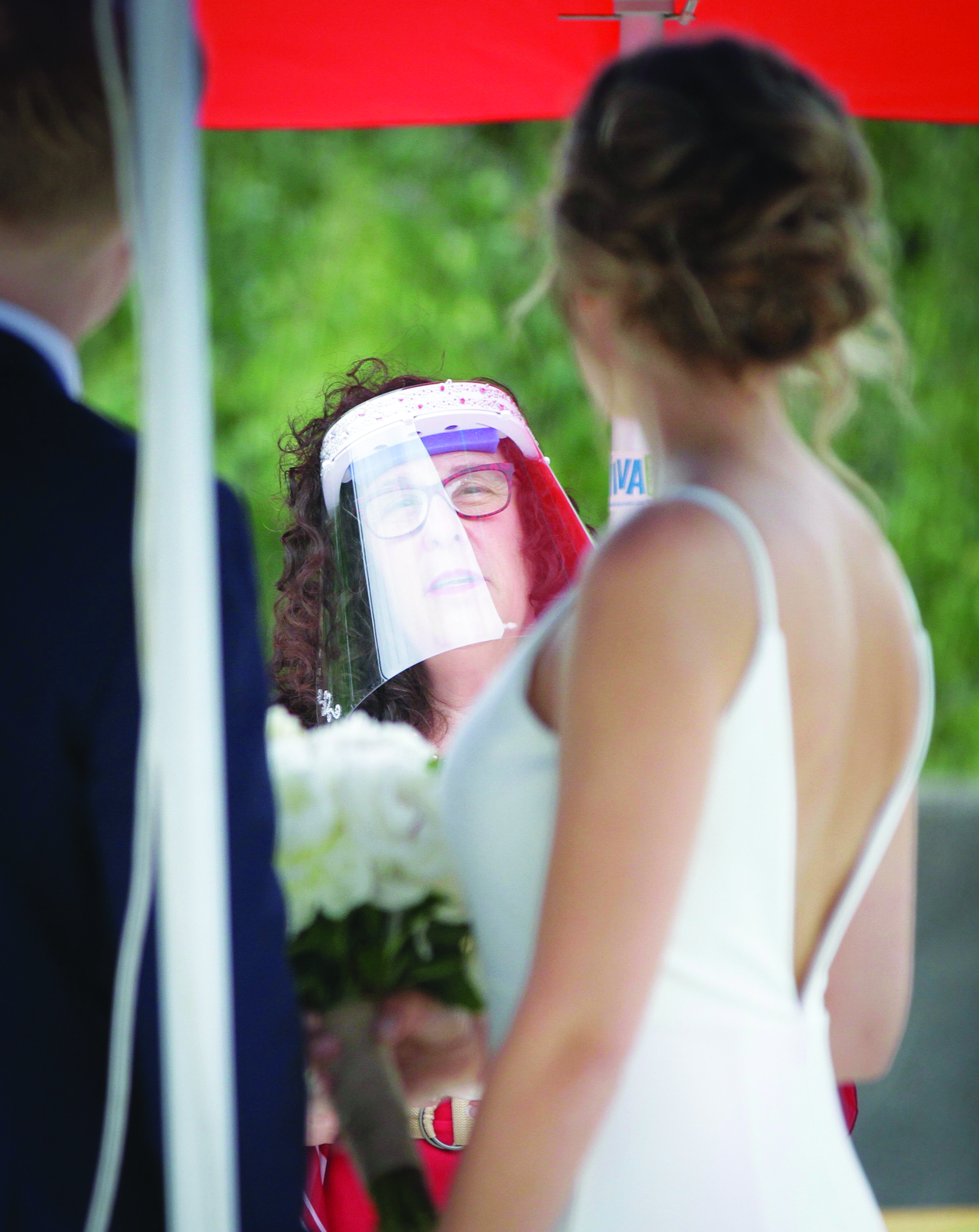 A bride stands in front of an officiant wearing a face shield