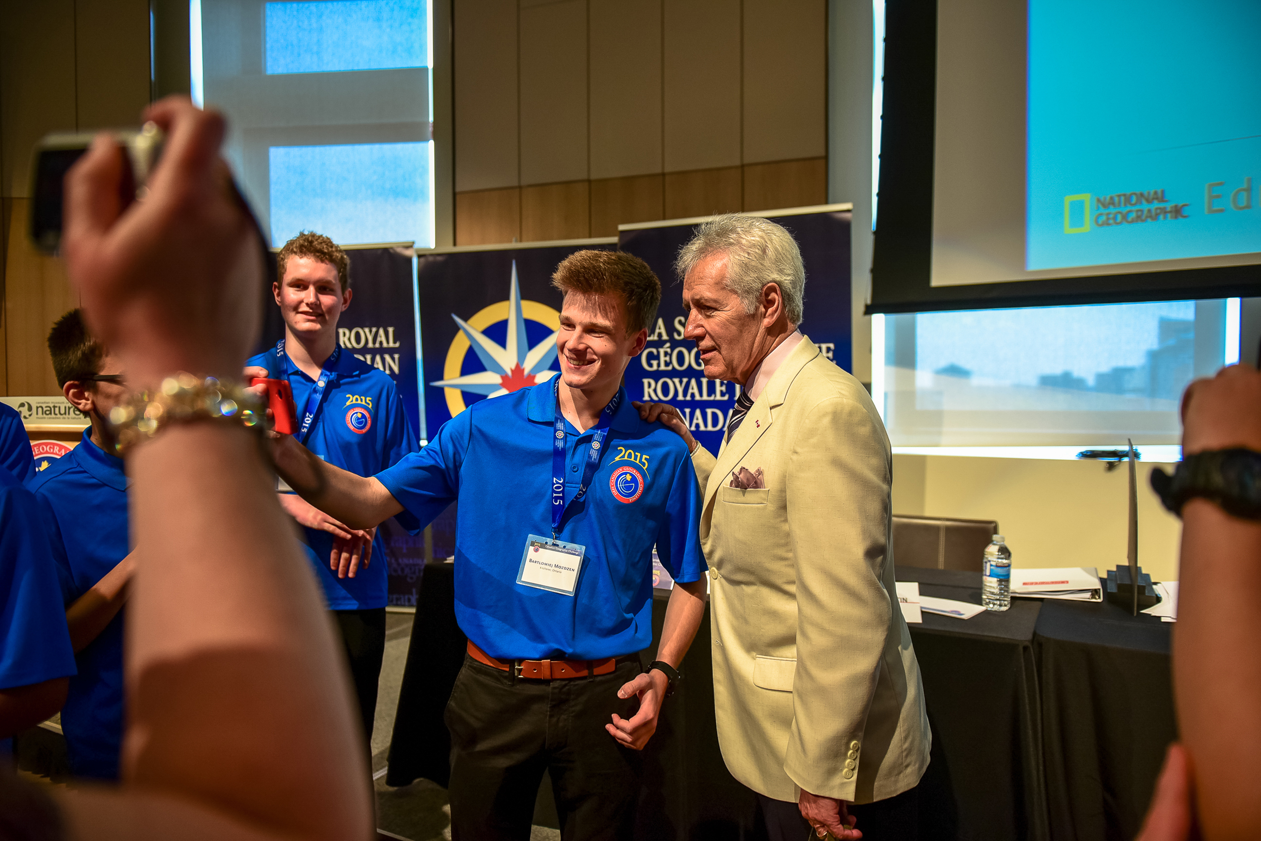 Alex Trebek poses for a photo with Can Geo Challenge finalists
