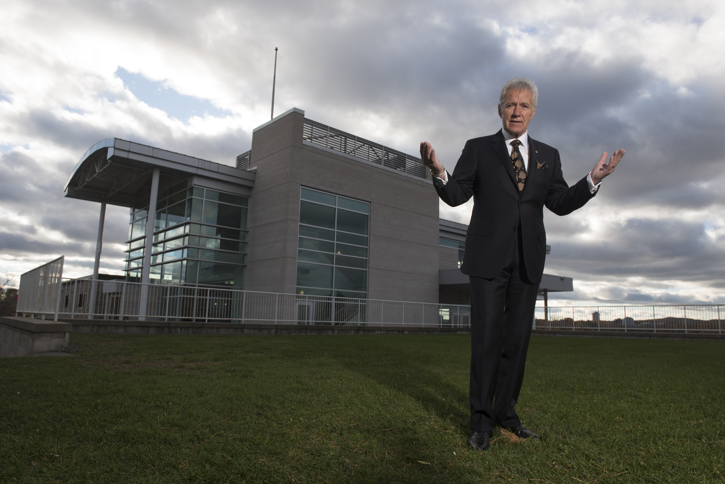 Alex Trebek stands on grass with the Royal Canadian Geographical Society Headquarters behind him