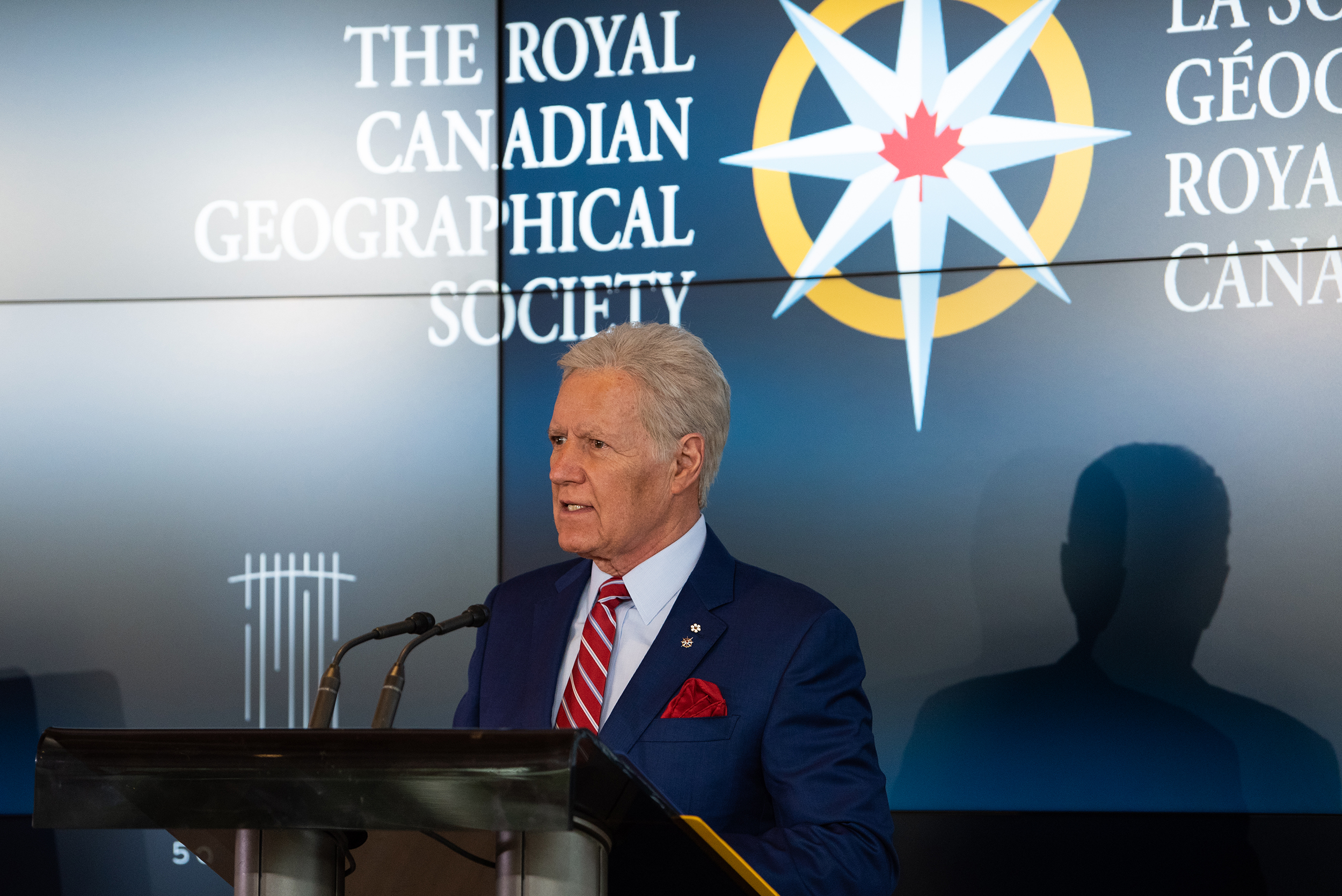Alex Trebek stands at a podium with the Royal Canadian Geographical Society logo on the screen behind him