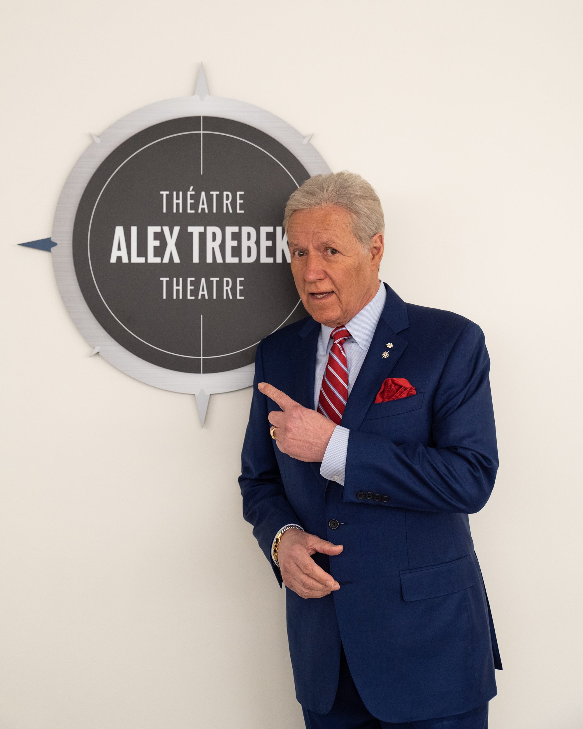 "Alex Trebek stands next to a sign that reads ""Théatre Alex Trebek Theatre"""