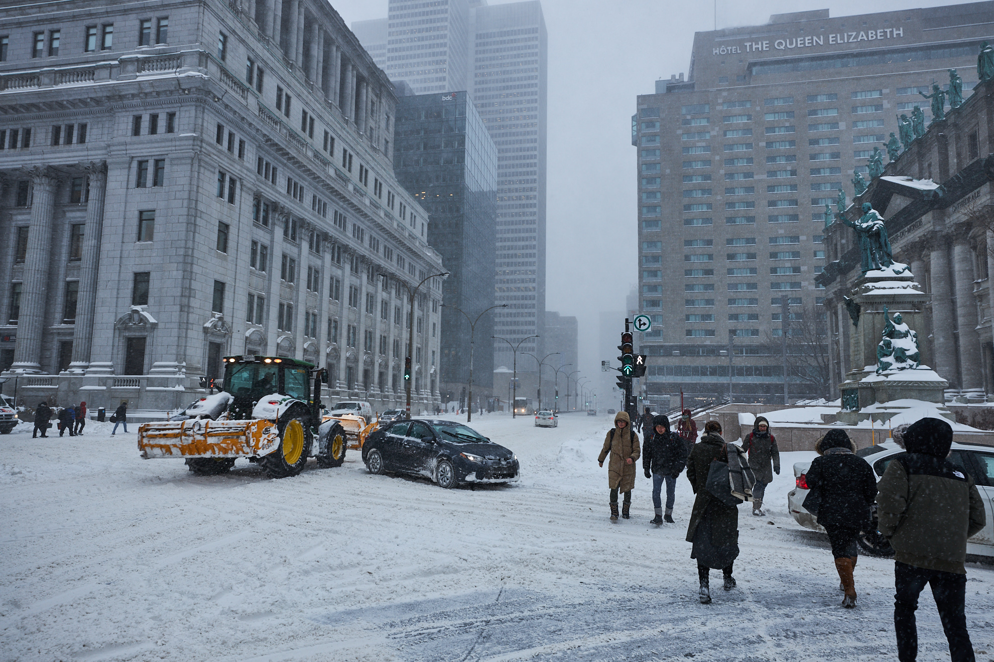 Pedestrians and cars cross a snowy intersection in downtown Montreal