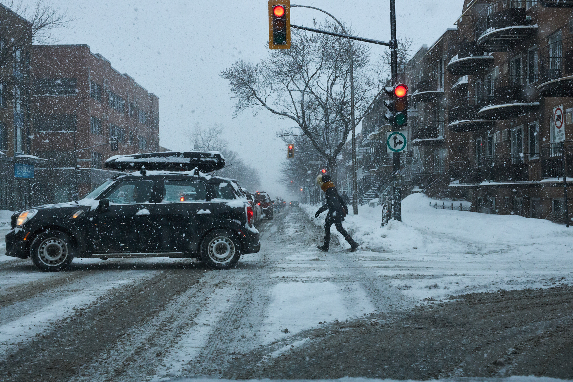Cars and pedestrians cross a snowy intersection in Montreal