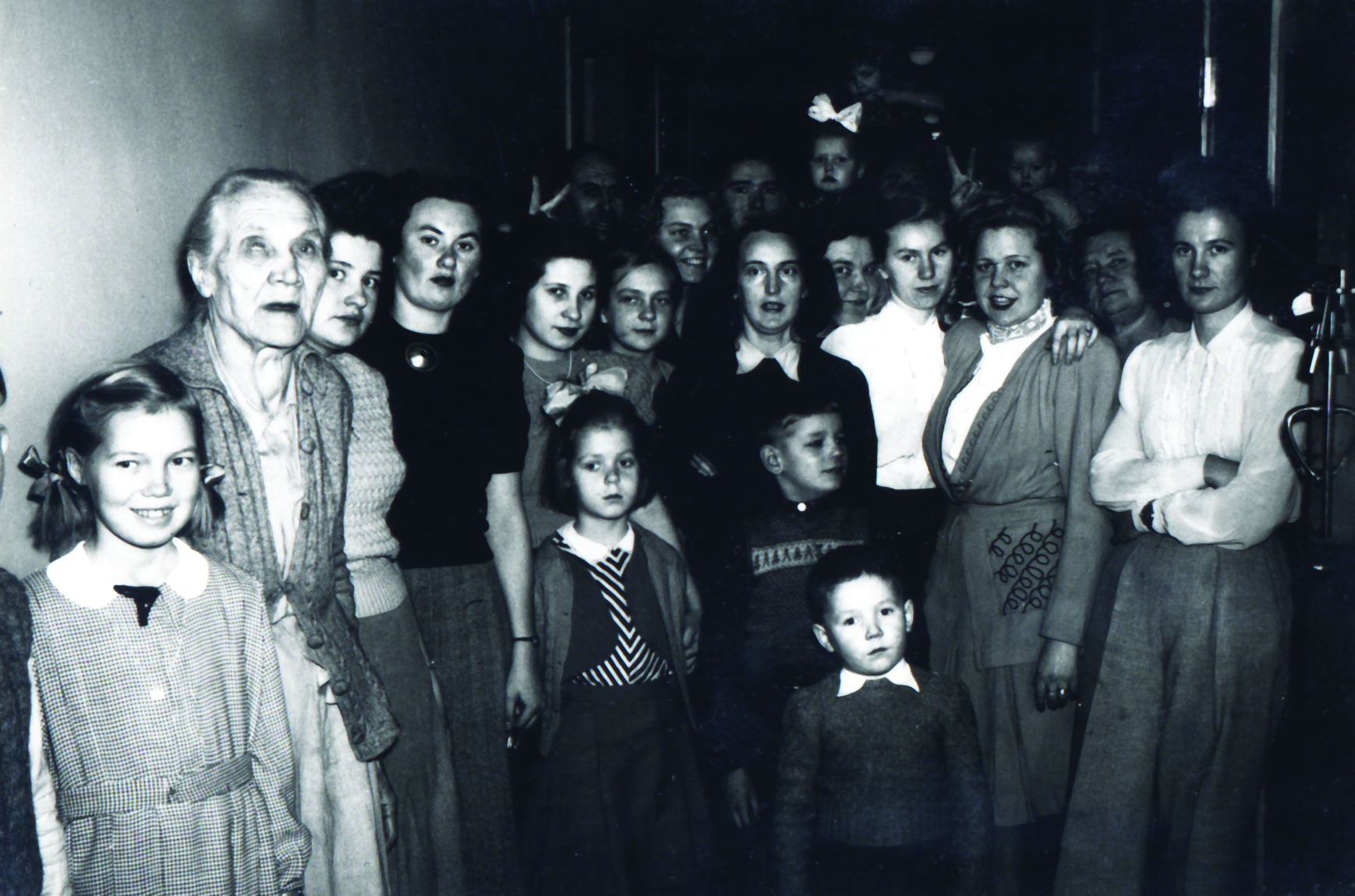 A black and white photo of women sitting and standing looking at the camera