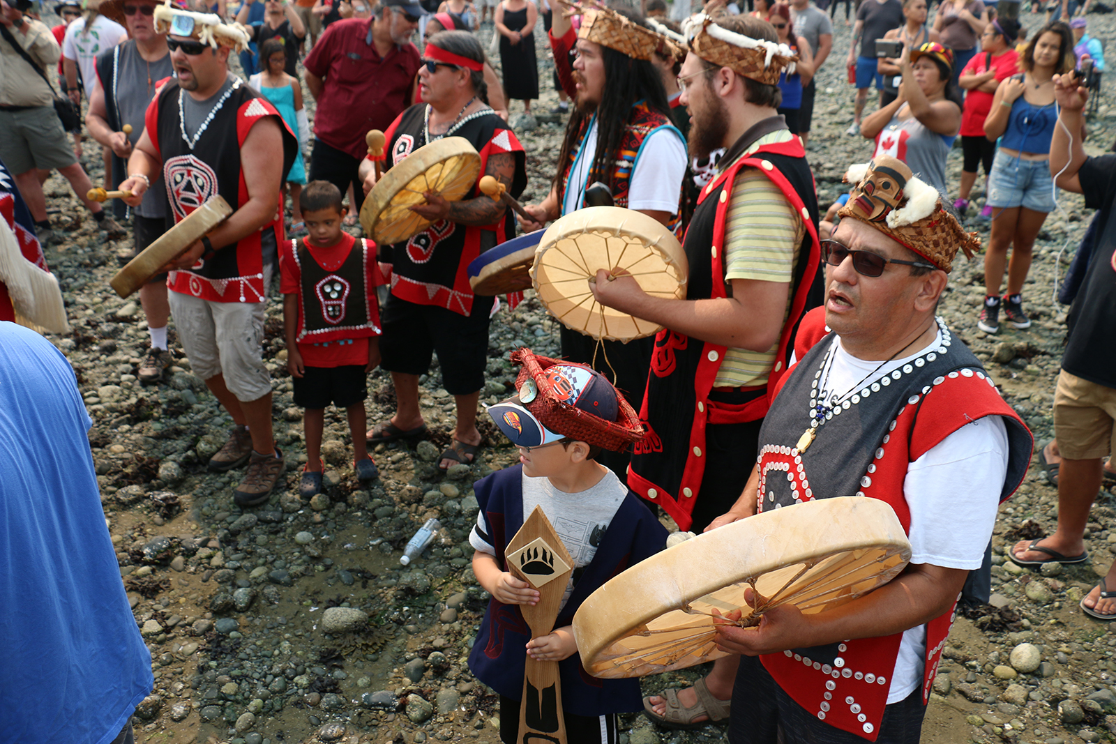A Lekwitok drum group sings visitors into Wei Wai Kum shores in Campbell River, B.C. on August 5. Master carver George Hunt Jr. stands among them at right.