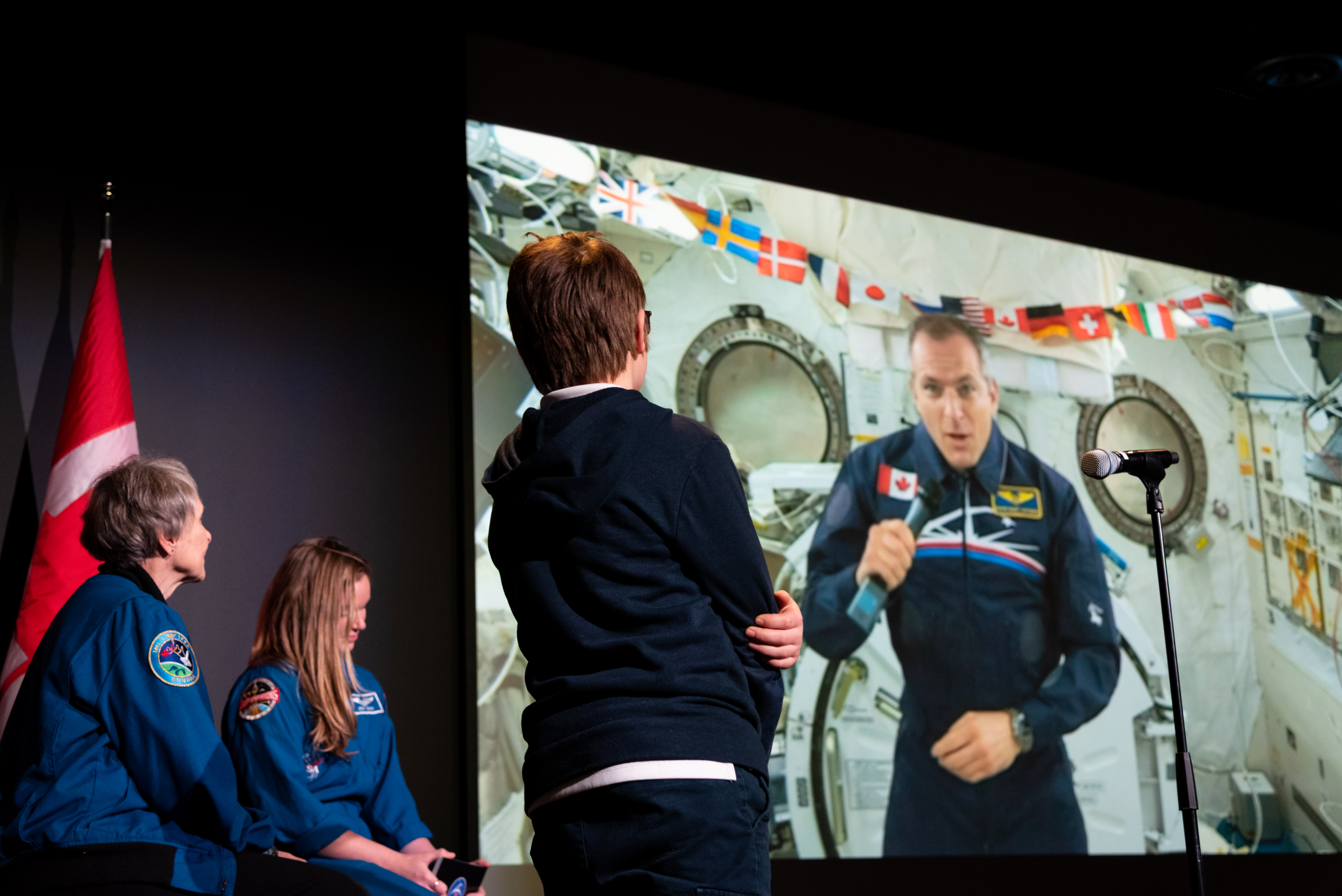 David Saint-Jacques, appearing via video link from the International Space Station, answers a student's question about space while Roberta Bondar, far left, and Jenni Sidey-Gibbons look on.