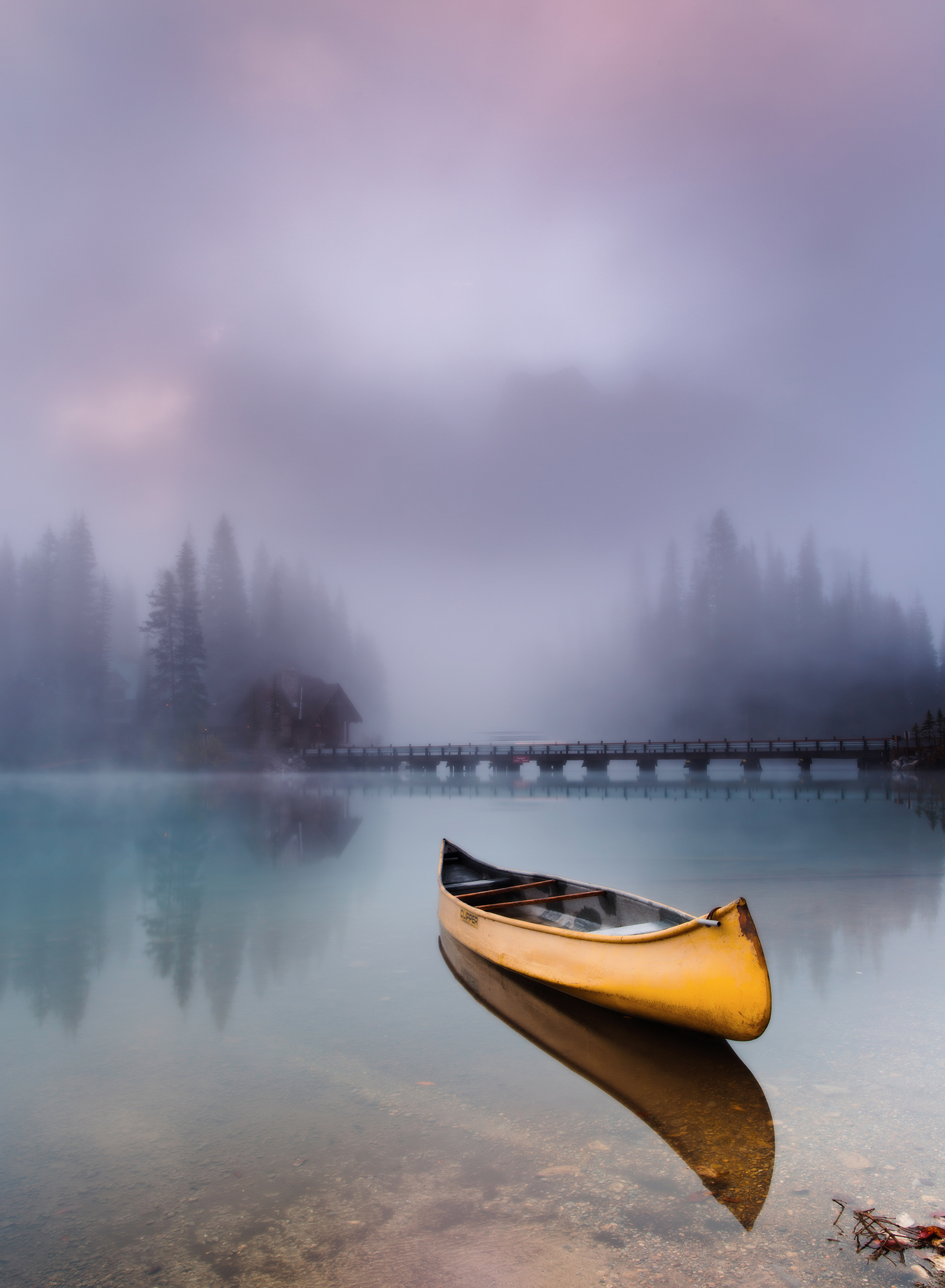 A canoe floats on the perfectly calm surface of Emerald Lake in B.C.'s Yoho National Park. Photo by Evgeny Chertov