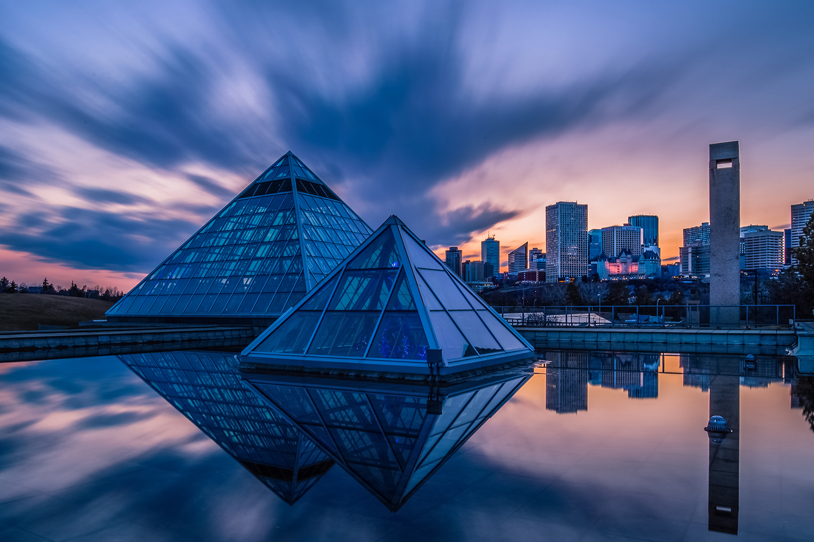 Edmonton's Muttart Conservatory is reflected in a puddle at sunset after a day of rain. Photo by Ron Huang