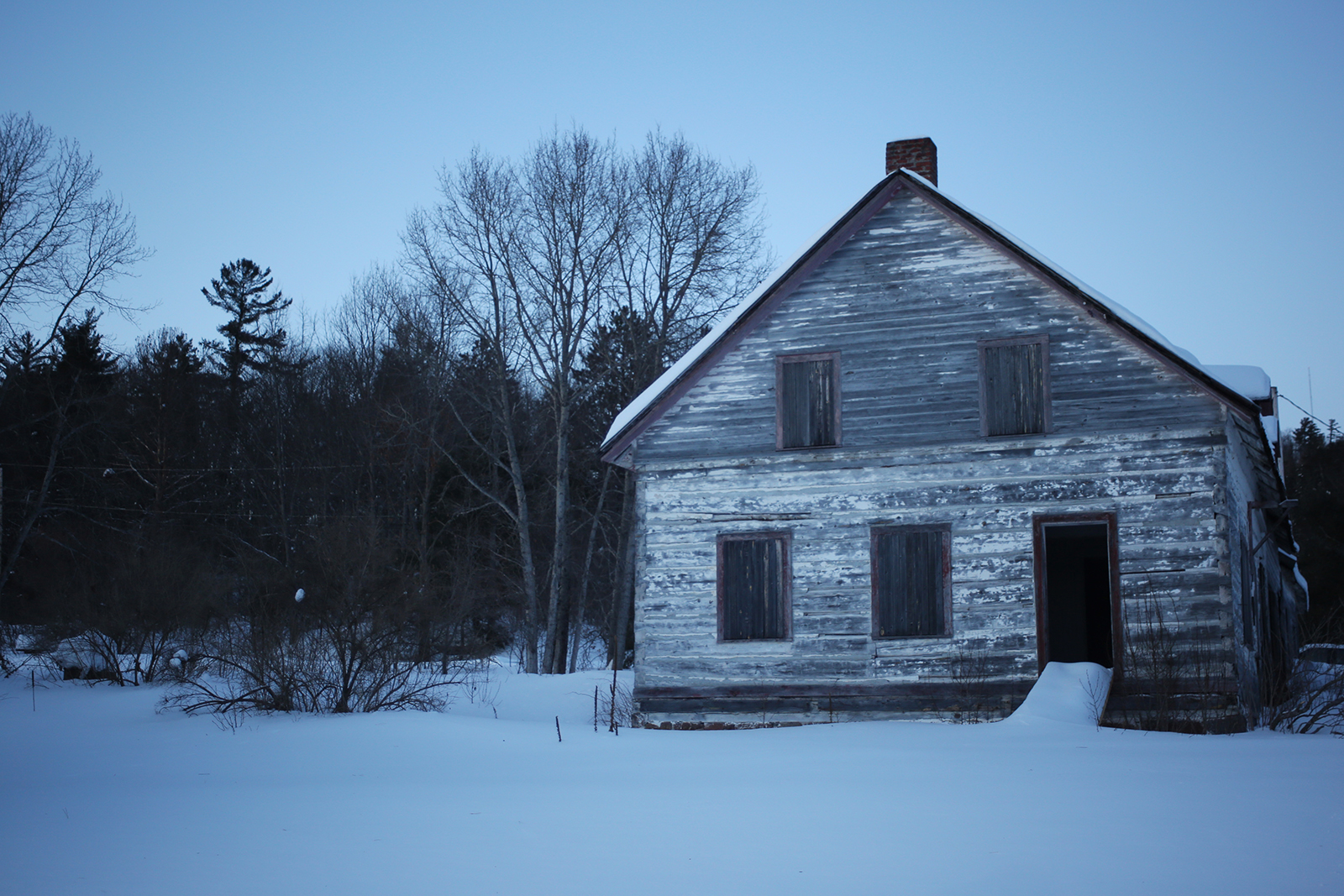 A weathered, abandoned building stands surrounded by deep snow and forest at dusk