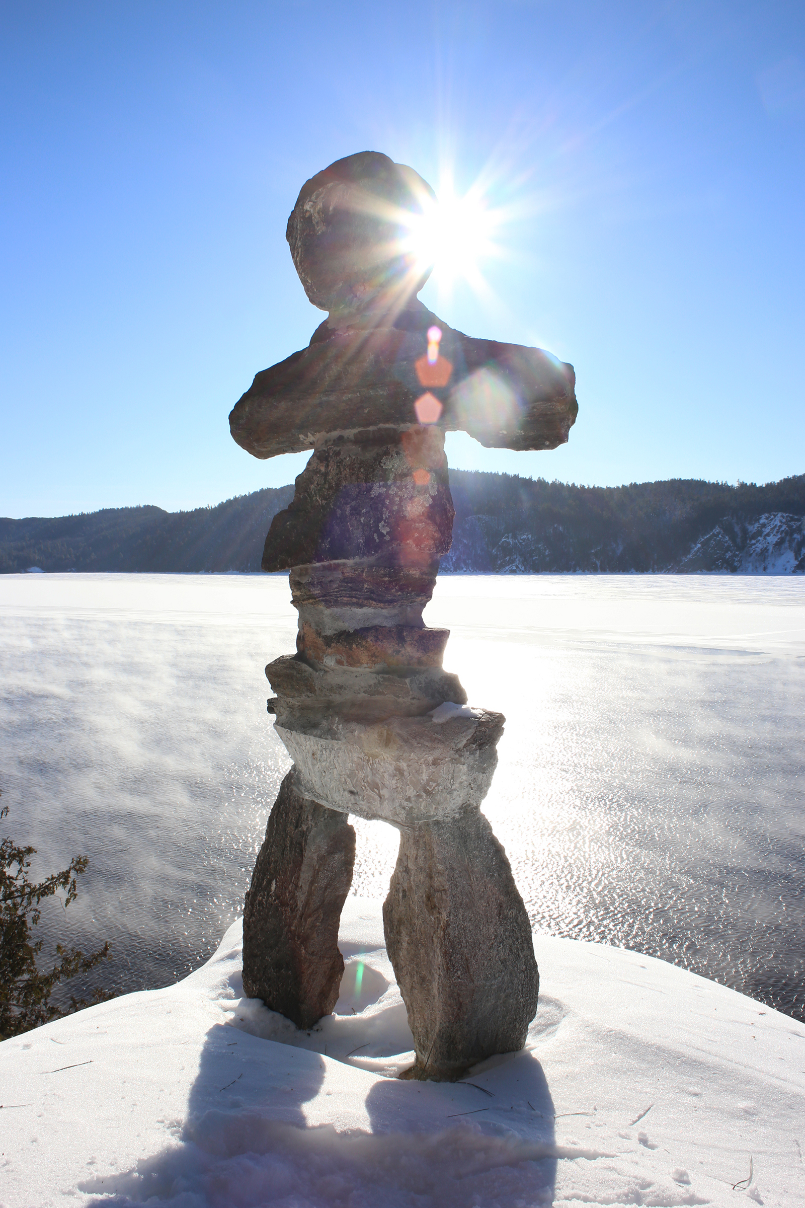 An Inukshuk overlooking a semi-frozen lake
