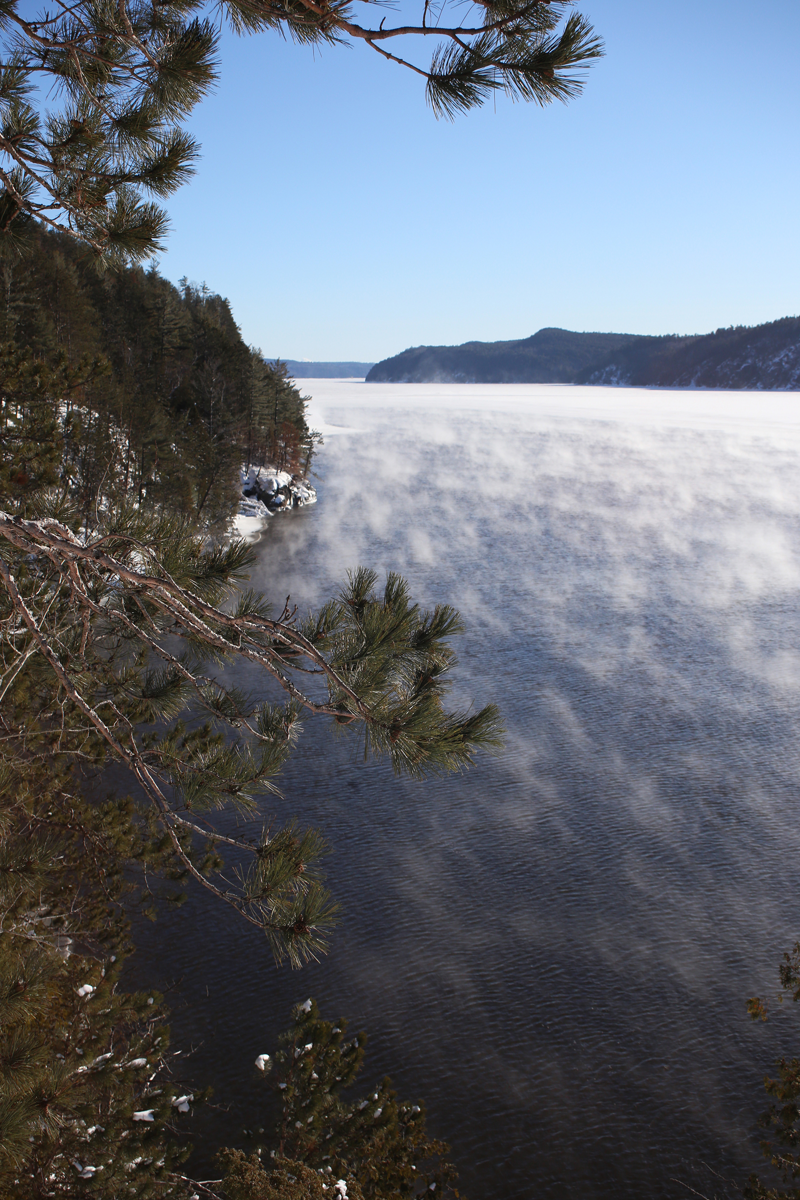 Steam rises from a long lake flanked by high cliffs on a winter morning