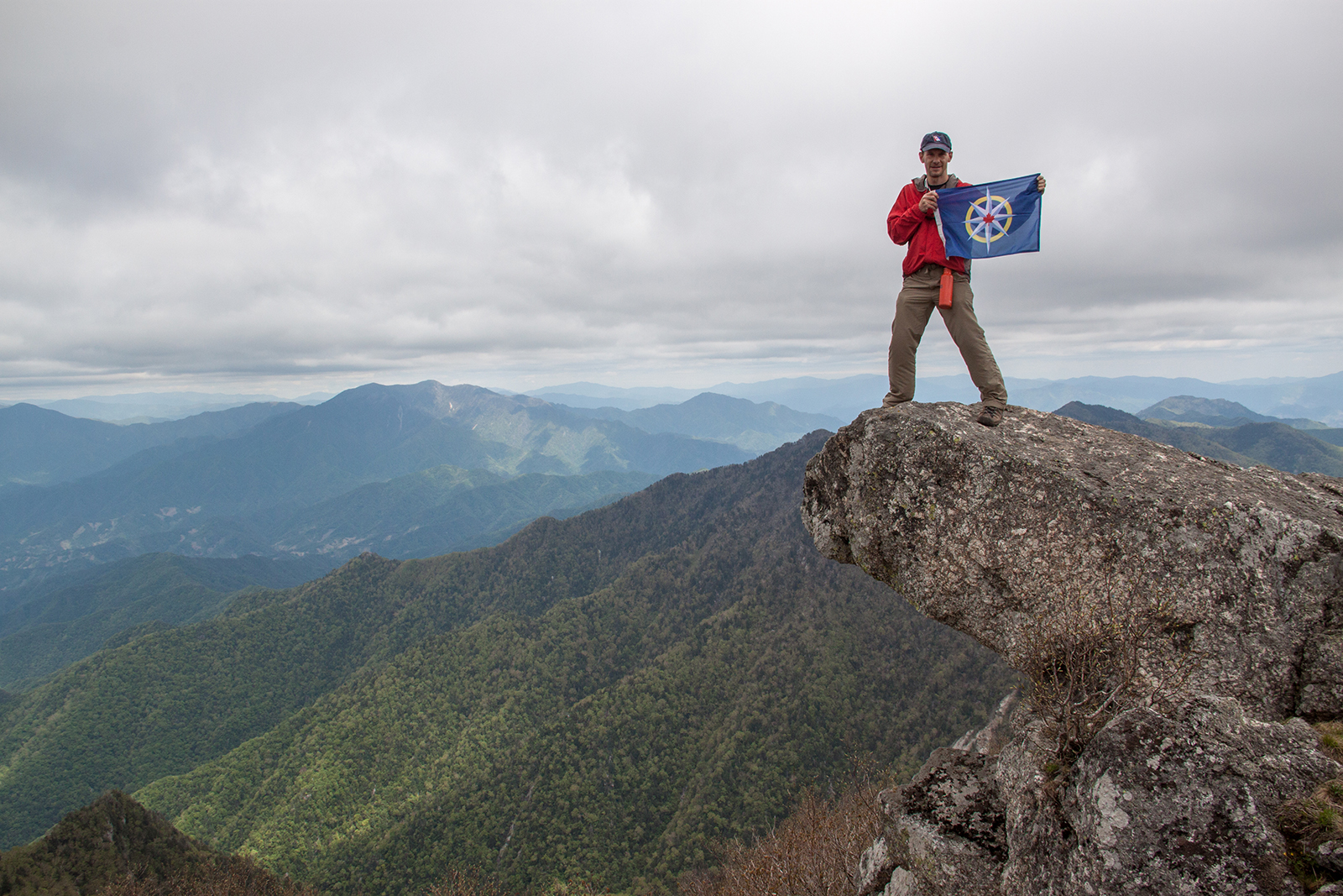 George Kourounis displays the flag of the RCGS atop Piro Peak, the tallest point in the Myohyang Mountains of central North Korea. (Photo courtesy George Kourounis)