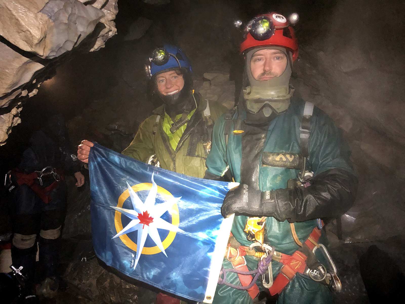 Kathleen Graham and Christian Stenner with the flag of the Royal Canadian Geographical Society inside Raspberry Rising cave