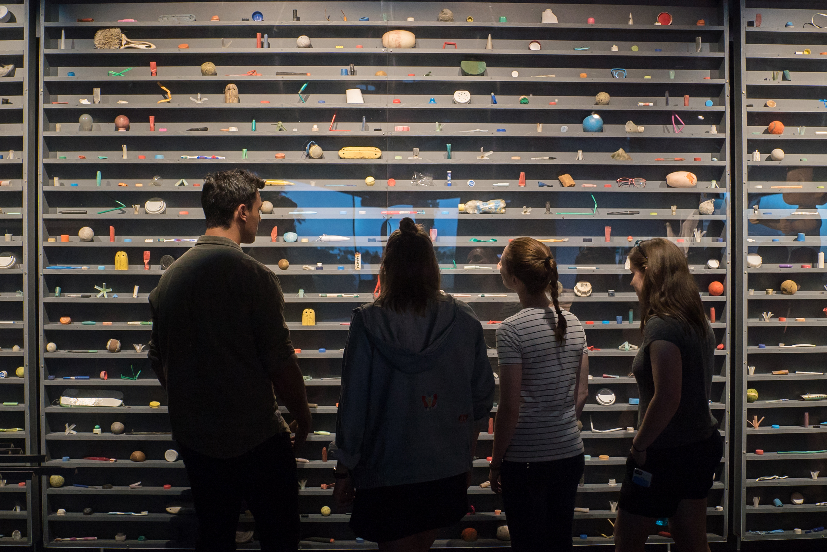Visitors examine a display of plastic debris recovered from the Pacific Ocean