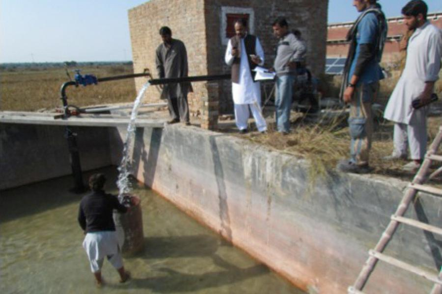 Technicians and farmers watch as an alternating-current solar-powered pump in Talagang, Pakistan