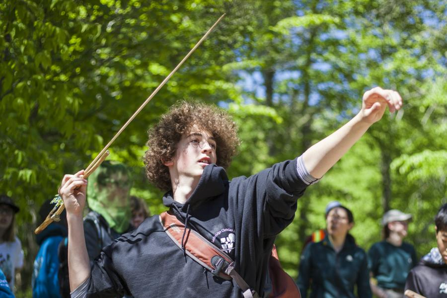 Student uses an atlatl to launch a dart
