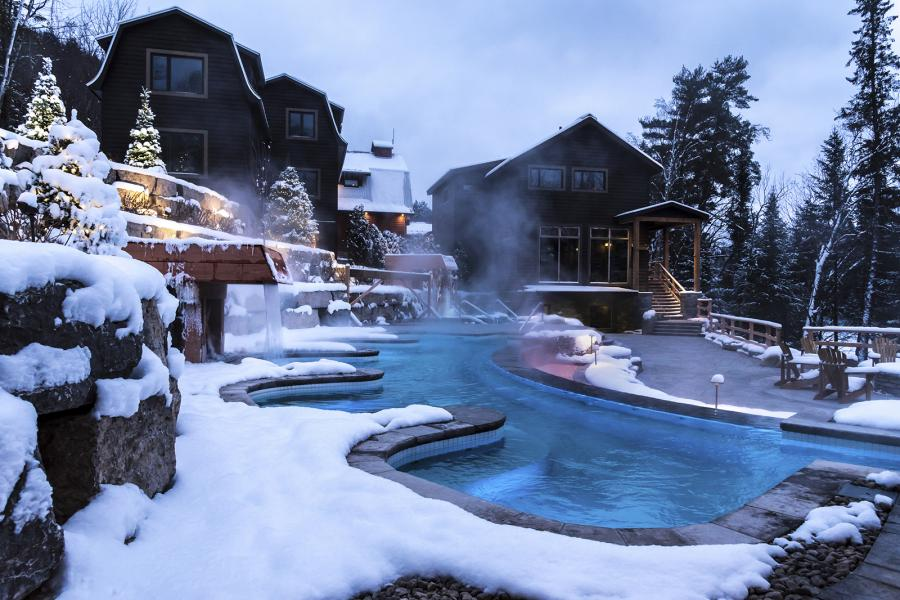 An infinity hot tub with snow around it at an outdoor Nordic spa