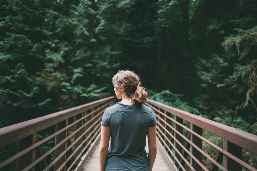 women on a bridge looking into a forest