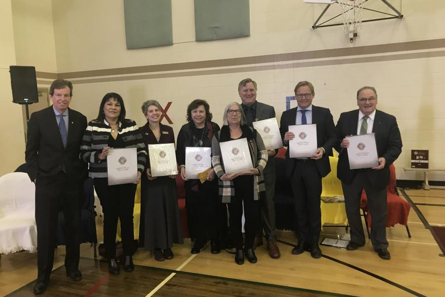 Alberta ministers and leaders stand together holding copies of the Indigenous Peoples Atlas of Canada