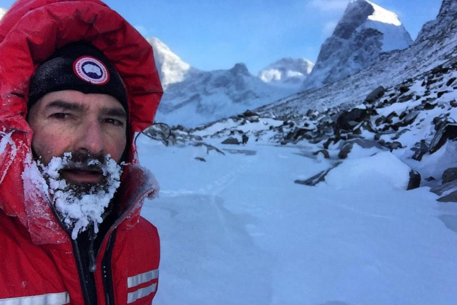 Canadian ultrarunner Ray Zahab, with his beard full of ice, against a snowy mountain backdrop