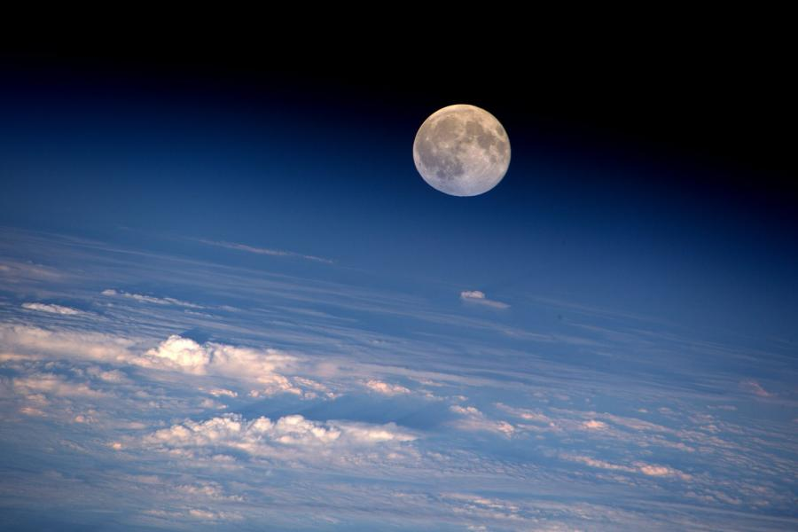 An amazing view of the full moon rising above a bed of clouds, as seen from the International Space Station