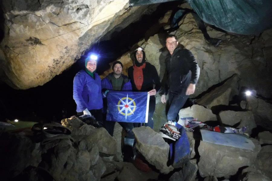Members of the Bisaro Plateau Caves Project hold the Royal Canadian Geographical Society flag