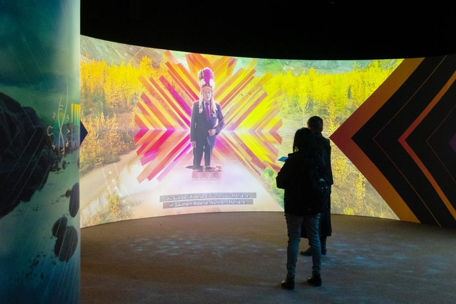 Two people watch a video at the UNCEDED exhibit