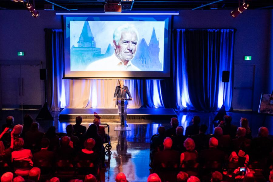 Alex Trebek gives his remarks on stage at the official opening event of 50 Sussex
