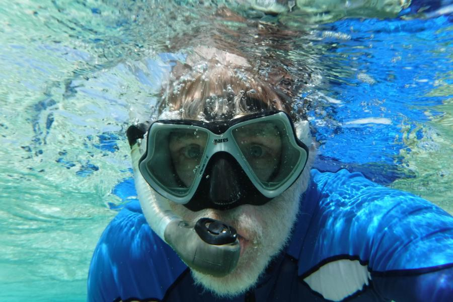 Man wearing snorkel mask under water
