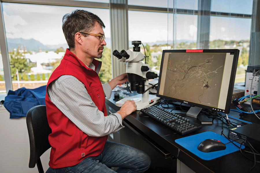 Ross in the Vancouver Aquarium Marine Science Centre analyzing water samples. Credit is: Steven Hargreaves