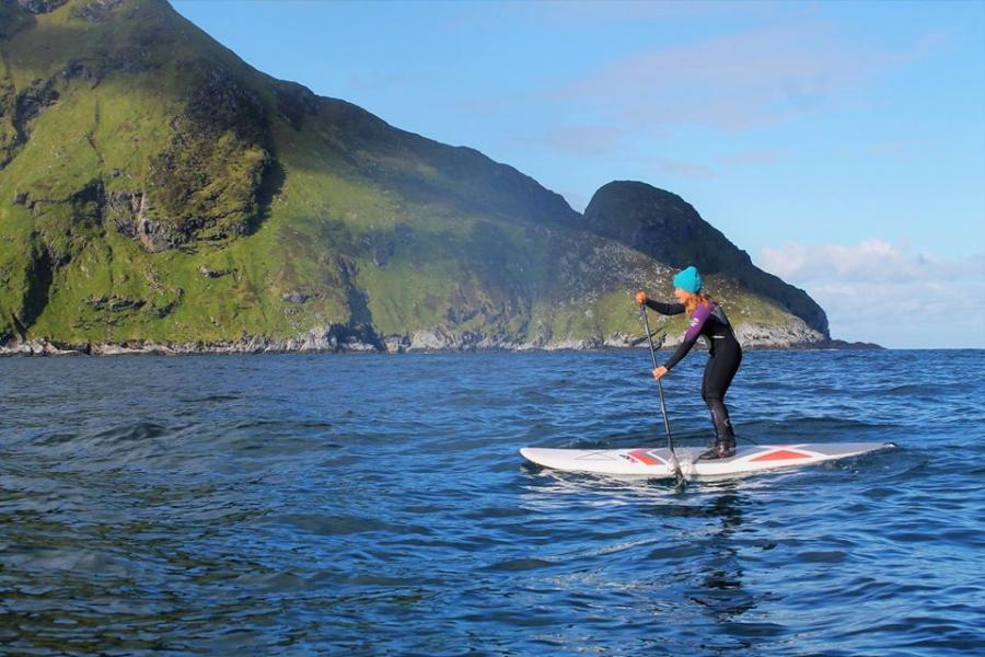 A woman paddles a stand up paddleboard in the water