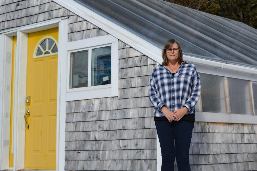 New Brunswick teacher stands in front of greenhouse as part of environmental initiative