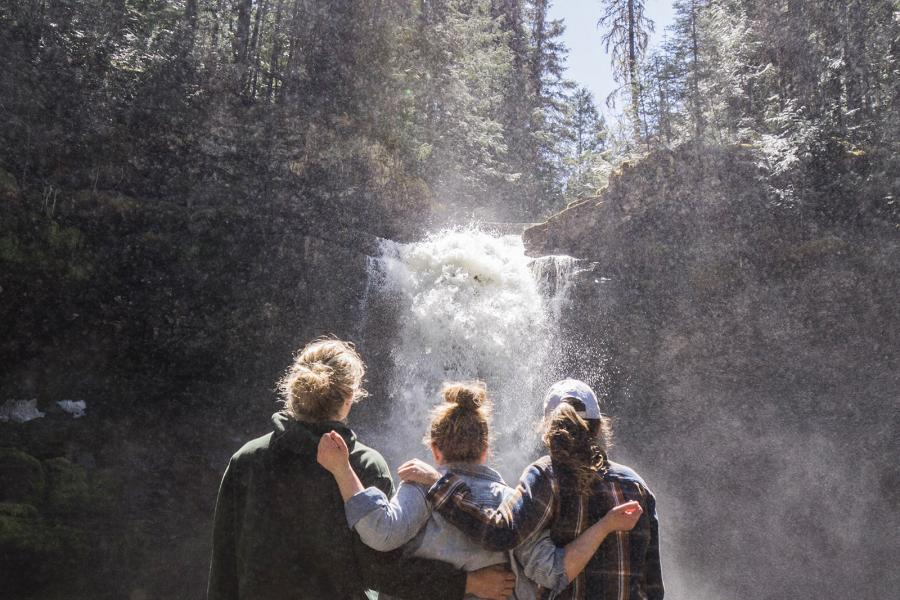 Three hikers stand with arms around each other looking at a waterfall