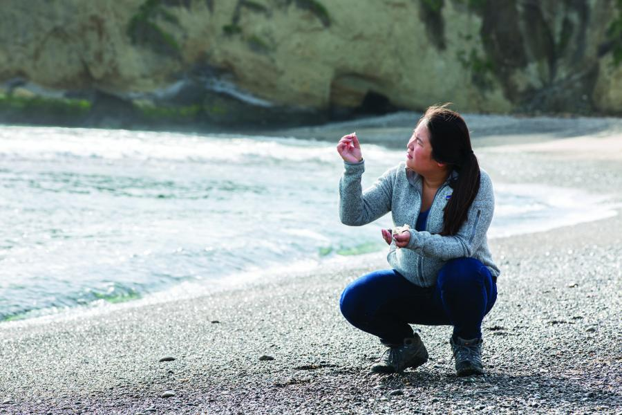 A woman squats on a beach and holds a rock close to her face.